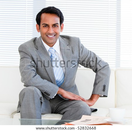 Handsome businessman sitting on the sofa in the office - stock photo
