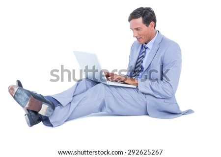 Handsome businessman sitting using his laptop on white background
