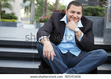 Handsome businessman smiling and sitting by the steps