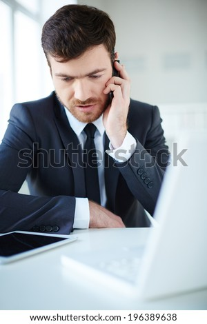 Handsome businessman speaking on the phone in office - stock photo