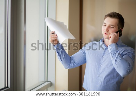 Handsome businessman, speaking on the phone in office - stock photo