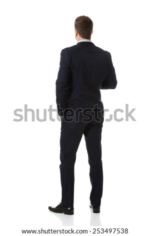 Handsome businessman standing back to camera. - stock photo