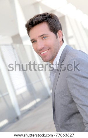 Handsome businessman standing in front of building