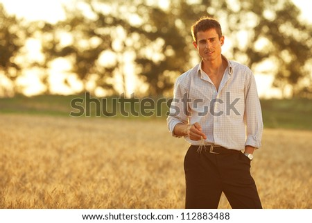 handsome businessman standing in the park. Sunlight everywhere. Outdoor shot. - stock photo