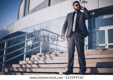 Handsome businessman standing on stairs in front of office building and using smart phone