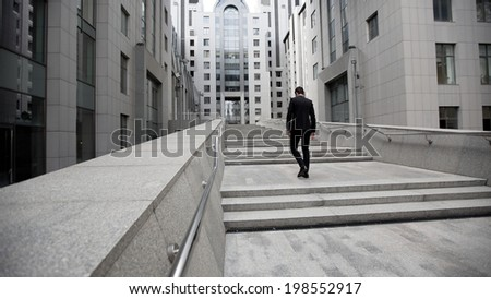 Handsome businessman standing on stairs of business center