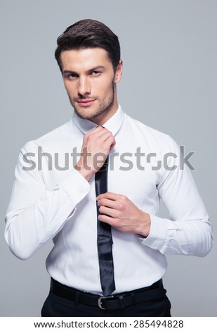 Handsome businessman straightening his tie over gray background and looking at camera - stock photo