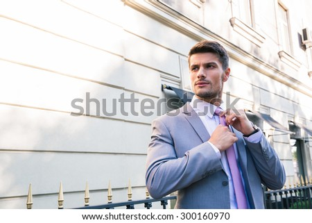 Handsome businessman straightens his tie outdoors - stock photo