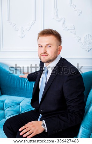 handsome businessman. Successful young man in a business suit sitting on the couch and smiling