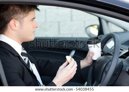 Handsome businessman talking on the phone in a car - stock photo