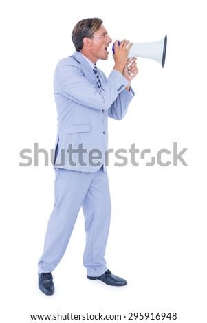 Handsome businessman talking through megaphone - stock photo