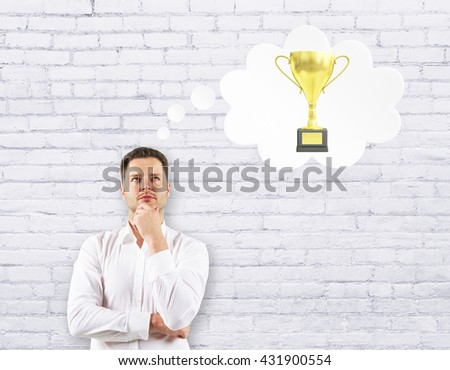 Handsome businessman thinking about golden cup trophy on white brick background - stock photo