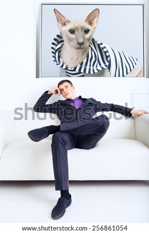 handsome businessman thinks, sitting on couch in his office - stock photo