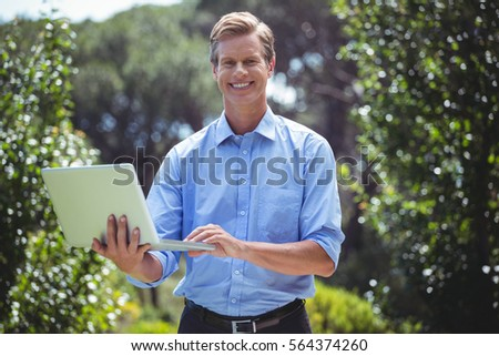 Handsome businessman using laptop outside