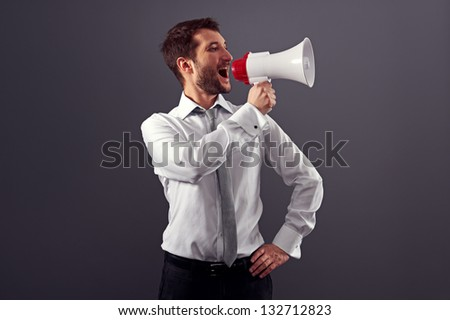 handsome businessman using megaphone over dark background in studio