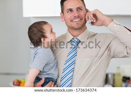 Handsome businessman using mobile phone while carrying baby boy in house - stock photo