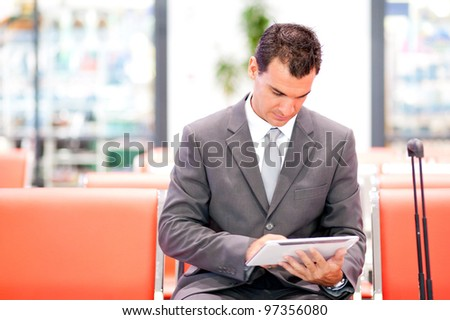 handsome businessman using tablet at airport - stock photo