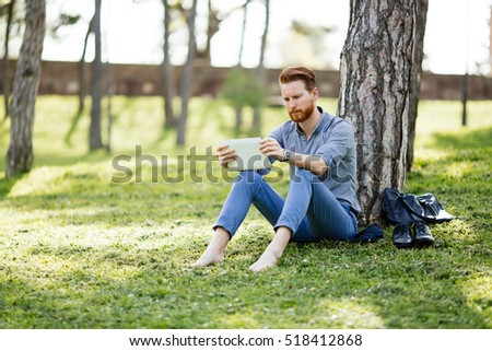 Handsome businessman using tablet pc in park