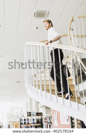 Handsome businessman walking down the stairs whilst holding a bag - stock photo