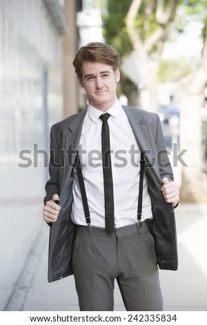 handsome businessman walking on sidewalk - stock photo