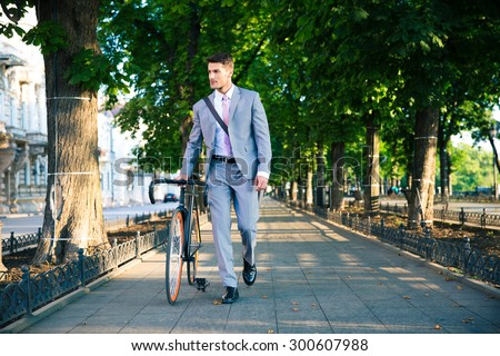 Handsome businessman walking with bicycle on the street in town  - stock photo