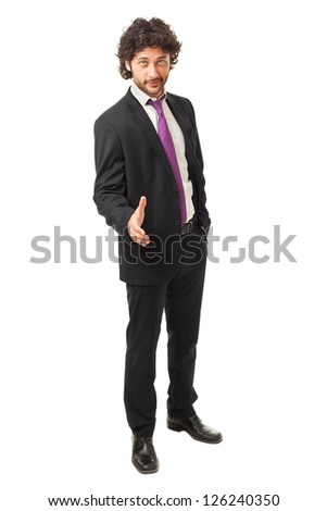 Handsome businessman wearing a suit and offering his hand for shaking over a white background