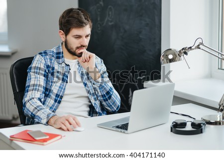 Handsome businessman wearing casual clothes working with laptop in office. concentrated man using computer - stock photo