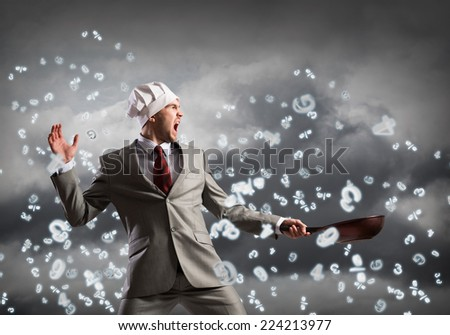 Handsome businessman wearing cook hat with pan in hands