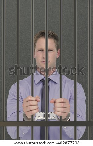 Handsome businessman wearing handcuffs against grey background - stock photo