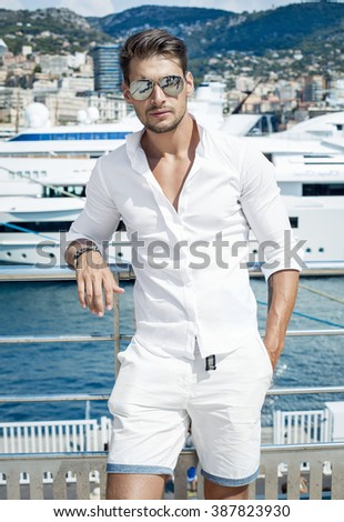 Handsome businessman wearing white clothes and sunglasses posing in port - stock photo