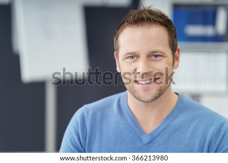 Handsome businessman with a friendly smile looking into the camera as he sits in the office in a casual shirt