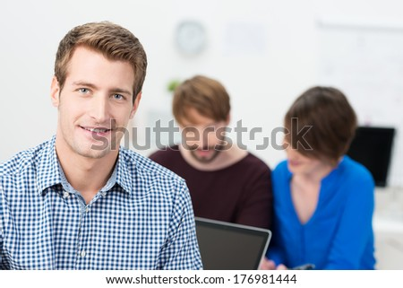 Handsome businessman with a friendly smile posing in the office in front of two hardworking colleagues - stock photo
