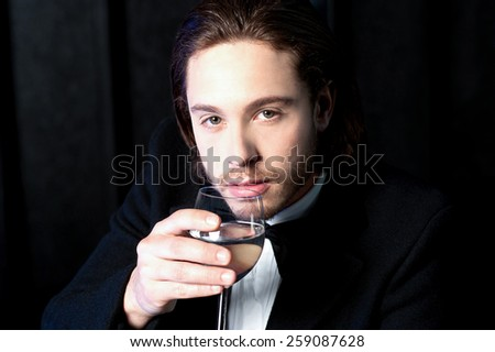 Handsome businessman with a glass of appetizer - stock photo