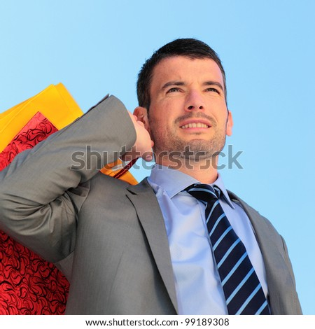 handsome businessman with bags and blue sky - stock photo