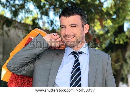 handsome businessman with bags outdoor before christmas