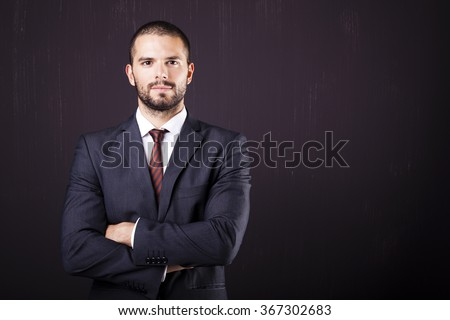 Handsome businessman with crossed arms against dark background
