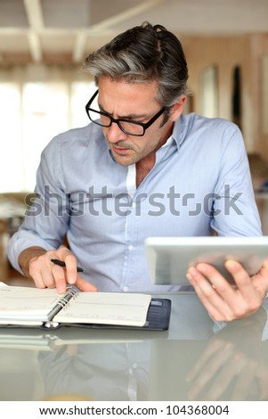 Handsome businessman with eyeglasses working from home - stock photo