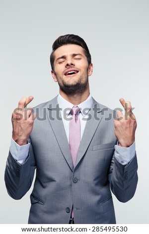 Handsome businessman with fingers crossed over gray background - stock photo