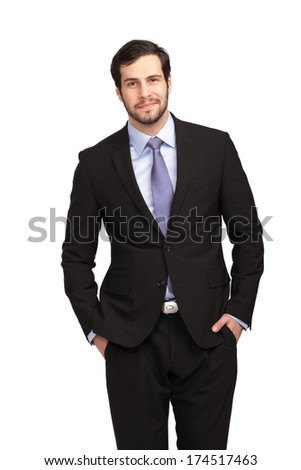 handsome businessman with hands in pockets smiling