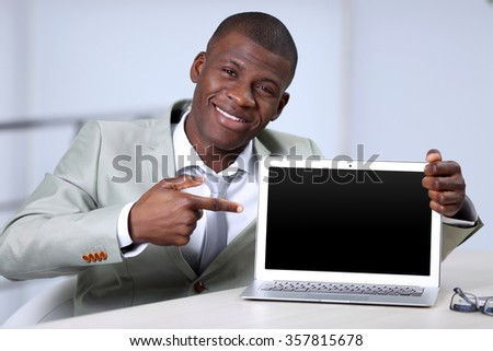Handsome businessman with laptop, close up - stock photo