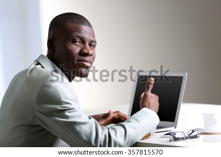 Handsome businessman with laptop in his office, looking over shoulder - stock photo