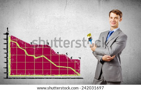 Handsome businessman with paint brush in hand