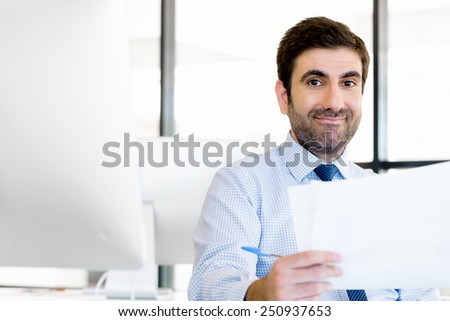 Handsome businessman with papers in office
