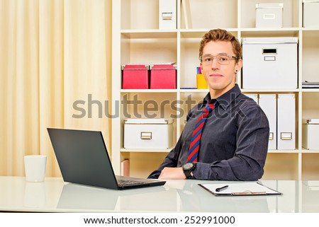 Handsome businessman working at the office on his laptop and friendly smiling at camera.