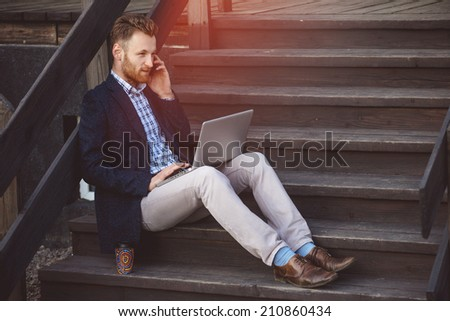 Handsome businessman working with laptop. Lightleak effect and instagram filter - stock photo