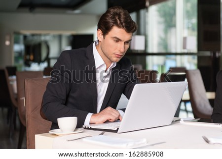 Handsome businessman working with laptop. Sitting at the restaurant and drinking coffee.