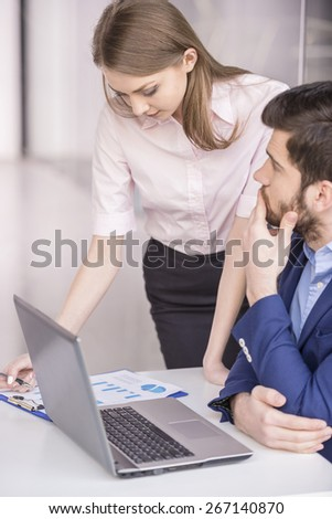 Handsome businessman working with laptop with his secretary.