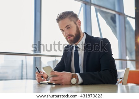 Handsome businessman writing notes from smartphone at modern office