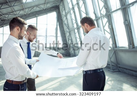 Handsome businessmen are discussing a business plan. They are holding a blueprint and looking at it with concentration. The man is pointing his finger on the diagram