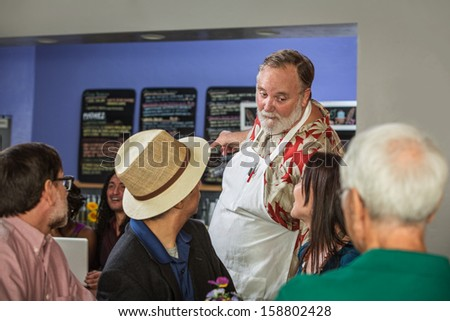 Handsome cafe barista showing customers menu - stock photo